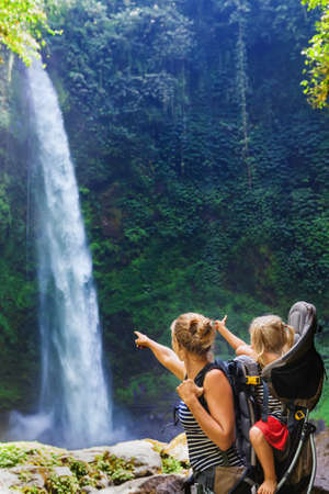 Young happy woman hold little traveller in back baby carrier, explore jungle waterfall in rainforest. Hiking activity adventure and fun with child on family summer vacation travel, weekend nature tour