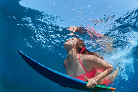 Young girl in bikini in action - surfer with surf board dive underwater with fun under big ocean wave. Family lifestyle, people water sport lessons, beach extreme swimming activity on summer vacation photo