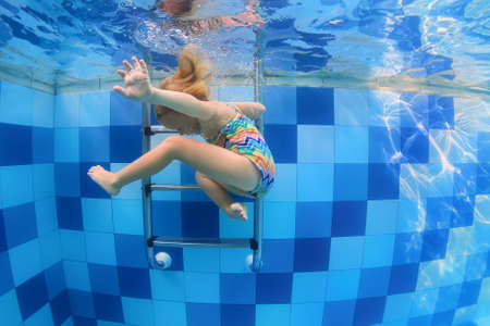 Funny photo of baby girl swimming and diving in pool with fun - jumping deep down underwater with splashes and foam. Family lifestyle and summer children water sports activity and lessons with parents Foto de archivo