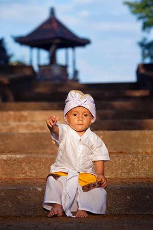 Porträtt av balinesisk bebispojke med leende ansikte i traditionell kostym Sarong sitter i hinduiskt tempel vid religiös ceremoni. Bali island barn och nationell kultur och etnisk konst av indonesiska människor.