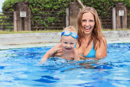 mum and child: Photo of happy family - swimming and having fun woman and little child in goggles. Focus on baby. Family lifestyle and water sport activity, swimming lessons with parents in pool on summer vacation.