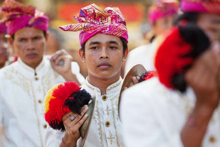 BALI, INDONESIA - JUNE 13, 2015: Young musician man of traditional Balinese people orchestra Gamelan in Balinese style male costume playing ethnic music on ceremony procession at Art and Culture Festival.