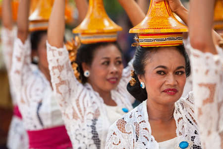 adult indonesia: DENPASAR, BALI ISLAND, INDONESIA - JUNE 13, 2015: Group of beautiful women in traditional Balinese costumes carry on head religious offering for hindu ceremony on parade at art and culture festival.