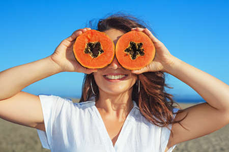Funny photo of positive adult woman with smiling face holding in hands ripe fruit - orange papaya slices. Healthful food, low calories breakfast on sea beach Healthy lifestyle on summer family holiday Standard-Bild