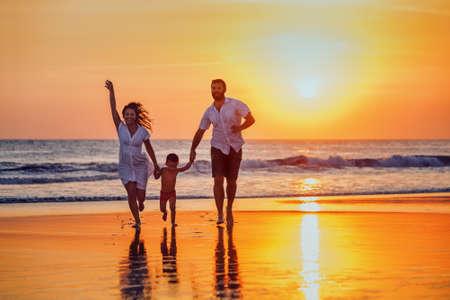 Gelukkig gezin - vader, moeder, baby zoon hand in hand en lopen met leuke langs zee zonsondergang surfen op zwart zand strand. Actieve ouders en mensen outdoor activiteiten op tropische zomer vakanties met kinderen.