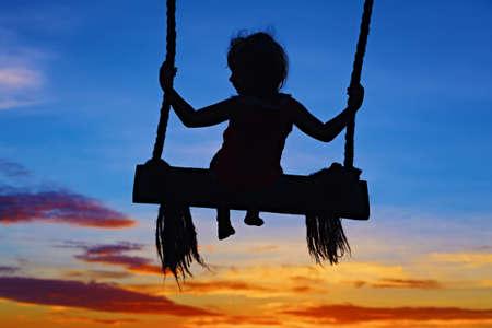 silueta niño: Negro silueta de niña volando alto con la diversión en columpio de cuerda en azul cielo naranja atardecer de fondo. el estilo de vida del viaje, la actividad de las personas playa de vacaciones de verano en familia con el niño en la isla tropical.