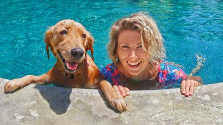 Grappig portret van glimlachende vrouw spelen met hond en opleiding golden retriever puppy in blauwe zwembad. Populaire hondenrassen, outdoor activiteiten en leuke spelletjes met familie huisdier op de zomer strandvakantie.