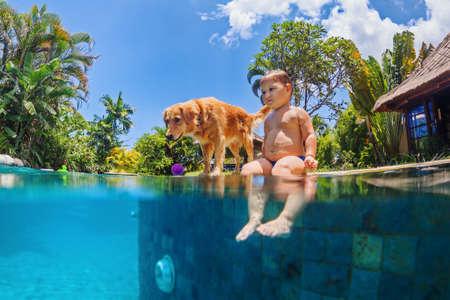 perros graciosos: foto subacuática divertida del pequeño bebé y el perro nadar en azul piscina al aire libre. Los niños de actividades deportivas de agua y clases de natación, entrenamiento de perros, juegos divertidos con mascota de la familia en la playa de vacaciones de verano. Foto de archivo