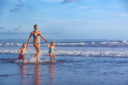 Happy barefoot family having fun - mother, baby son, daughter together run with splashes by water pool along surf of sunset sea beach. Active parent and people activity on summer holiday with children Stock Photo