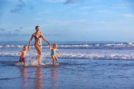 Lycklig barfota familj ha roligt - mor, baby son, dotter k�r tillsammans med st�nk av vatten poolen tillsammans surfa p� solnedg�ngen havet stranden. Aktiv f�r�lder och folk aktivitet p� sommarsemester med barn Stockfoto