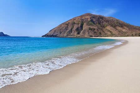 desert island: Beautiful scene on best desert beach with white sand, clear water on ocean bay Mawun in tropical island Lombok. Stock Photo