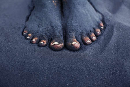 dirty feet: Photo of dirty woman bare feet in black sand. People relaxation, fun and walking barefoot by black volcanic sand on ocean beach.