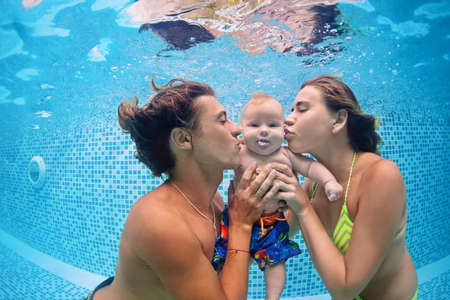 Happy swimming family - father and mother with baby swim and dive underwater with fun in swimming pool. Stock Photo