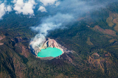 Aerial photo of active volcano Ijen in East Java - largest highly acidic crater lake in world with turquoise sulphuric water. Site of sulfur mining.
