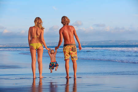 Happy family - father, mother, baby son hold hands, swim with fun, walk along sunset sea surf on black sand beach.