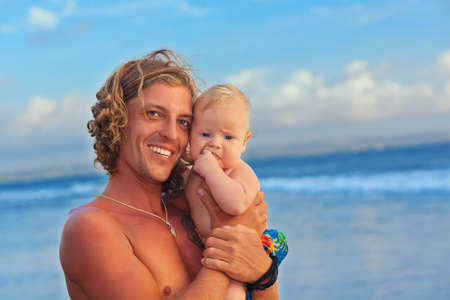 two generations: Happy family on sea beach - surfer and little son. Father with baby boy have fun on blue ocean surf and sunset sky background Stock Photo