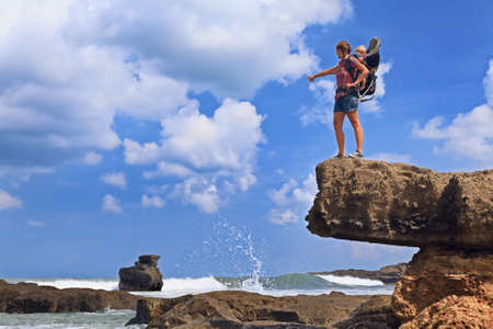 sea cliff: Nature walk on sea beach. Happy mother high rock cliff hold little traveller in carrying backpack. Baby ride on woman back. Travel adventure, hiking with child carrier, family summer vacation on Bali. Stock Photo