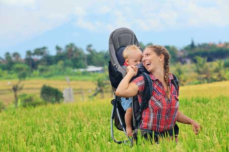 Vandring i grönt ris terrass fält. Lycklig mor hålla lite resenären i ryggsäck. Baby rida på kvinnan tillbaka. Rese äventyr, vandring med barn bärare, familj semester på Bali.