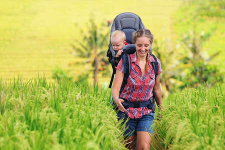Nature walk in green rice terrace field. Happy mother hold little traveller in carrying backpack. Baby ride on woman back. Travel adventure, hiking with child carrier, family summer vacation on Bali. Stock Photo