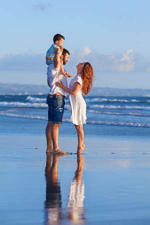 Glückliche vollständige Familie - Vater, Mutter, Baby-Sohn gehen mit Spaß entlang Rand Sonnenuntergang Meer surfen auf schwarzem Sandstrand. Aktive Eltern und Menschen Aktivität im Freien im Sommerurlaub mit Kindern auf der Insel Bali Standard-Bild