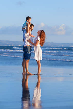 Happy full family - father, mother, baby son walk with fun along edge of sunset sea surf on black sand beach. Active parents and people outdoor activity on summer holiday with children on Bali island Stock Photo
