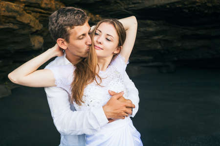 honeymooners: Happy family on honeymoon holiday - just married young man and woman hug with smile on black sand beach with rock background. Active lifestyle, people activity on summer vacation on tropic island.