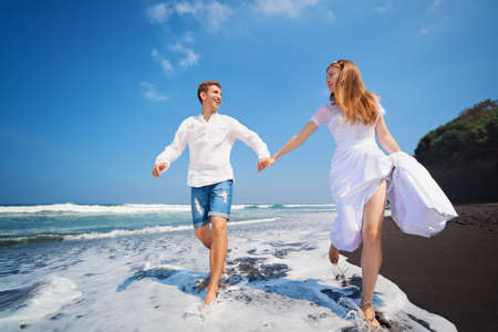 honeymooners: Happy family on honeymoon holiday - just married young man and woman run with fun by black sand beach along sea surf. Active lifestyle, people outdoor activity on summer vacation on tropic island.