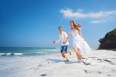 honeymooners: Happy newlywed family on honeymoon holiday - just married loving couple run with fun by black sand beach along sea surf. Active lifestyle, people outdoor activity on summer vacation on tropical island.