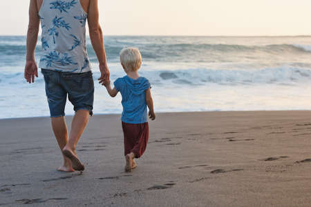 Happy family - barefoot father holds baby son hands, walk with fun along sunset sea surf on black sand beach. Travel, active parents lifestyle, people activity on summer vacations with children. Stock Photo