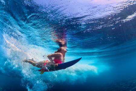 Young active girl wearing bikini in action - surfer with surf board dive underwater under big ocean wave. Family lifestyle, people water sport adventure camp and beach extreme swim on summer vacation.