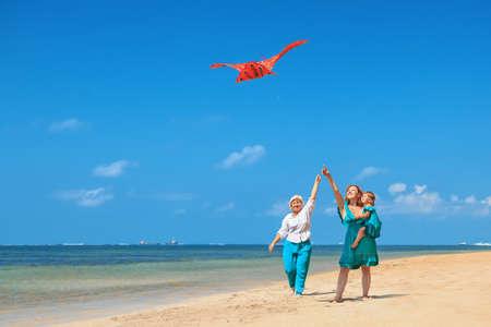 La familia feliz se divierte en la playa - la abuela, la madre y el bebé niña de pie junto olas del océano. Mujer mayor que se ejecuta con el vuelo del milano real. padres activos y personas actividad en vacaciones de verano con los niños.