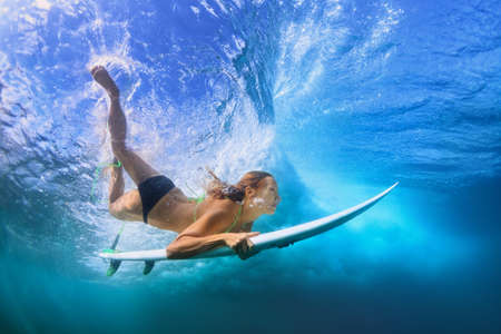 Young active girl in bikini in action - surfer with surf board dive underwater under breaking big ocean wave. Family lifestyle, people water sport adventure camp, beach extreme swim on summer vacation Standard-Bild