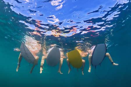 Les jeunes filles actives en bikini - surfeurs sont assis sur des planches de surf, attendez grande vague de l'océan. Photo sous-marine des pieds femelles. Les gens dans le sport de l'eau camp d'aventure, plage extrême baignade sur la plage de vacances d'été.
