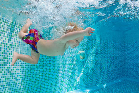 Funny photo of active baby swimming and diving in pool with fun - jump deep down underwater with splashes and foam. Family lifestyle and summer children water sports activity and lessons with parents.