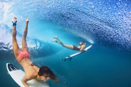 Active girls in bikini in action - surfers with surf board dive underwater under breaking big ocean wave. Family lifestyle, people water sport adventure camp, beach extreme swim on summer vacation