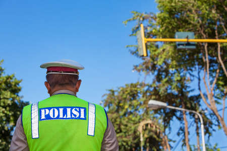 Indonesian police officer in fluorescent jacket standing on the street