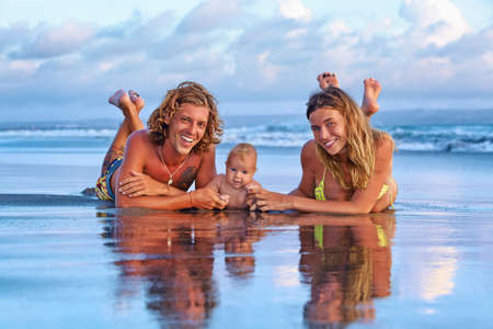 Happy family travel - father, mother, baby son walk with fun along sunset sea surf on black sand beach. Active parents lifestyle, people outdoor activity on tropical island summer vacation with child.