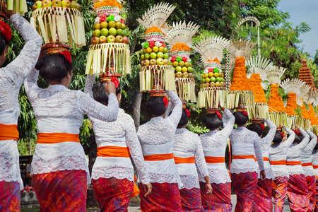 Procession av vackra balinesiska kvinnor i traditionella kostymer - sarong, bära erbjudande på huvuden för hinduisk ceremoni. Konstfestival, kultur på ön Bali och Indonesien, asiatisk resa bakgrund