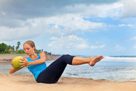 laying abs exercise: Fit woman stomach exercising on sand beach. Doing crunches core, leg raising and twisting exercises with coconut as weight. Woman doing abs workout. Fitness woman doing a sit up. Ocean surf background Stock Photo