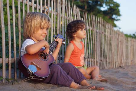 Weinig gelukkige jongen veel plezier, muziek afspelen op Hawaiiaans gitaar ukelele voor kleine baby meisje, genieten van zonsondergang oceaan strand. Kinderen gezonde levensstijl. Reizen, familie activiteit op tropisch eiland zomervakantie