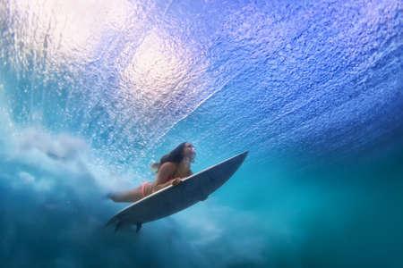 im Bikini Sportives Mädchen in Aktion. Surfer mit Surfbrett tauchen unter Wasser unter Ozeanwelle brechen. Gesunder Lebensstil. Wassersport, Schwimmen und extreme Surfen im Abenteuer-Camp auf Sommerstrandferien Standard-Bild