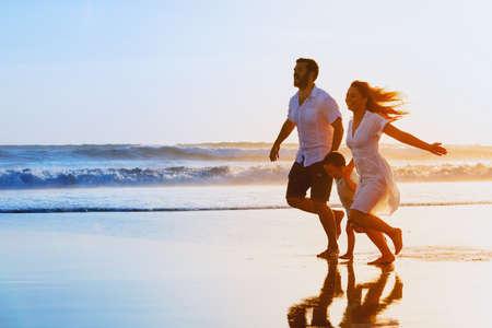 Familia feliz - padre, madre, hijo del bebé se dan la mano y se ejecutan en conjunto con la diversión a lo largo de surf puesta de sol en la playa de arena negro. Viajes, estilo de vida activo, los padres con niños en vacaciones de verano tropicales.