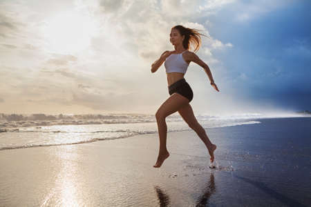 Active sporty woman run along ocean surf by water pool to keep fit and health. Sunset black sand beach background with sun. Woman fitness, morning workout and sport activity on summer family holiday.