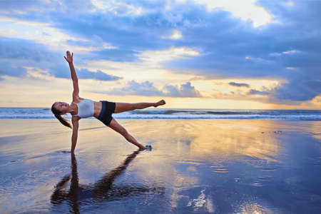 Active sporty woman stand in yoga pose on black sand beach to keep fit and health. Sunset blue ocean surf background with sun. Woman fitness, morning workout, sport activity on summer family holiday