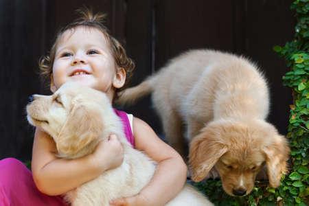幸せな赤ちゃんの女の子の面白い写真は美しいゴールデン ラブラドール ・ リトリーバーの子犬を抱っこ、一緒に遊ぶ。犬の訓練、家族のライフ ス