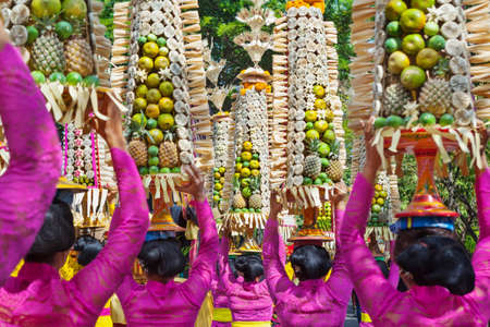 wonderful: Procession of beautiful Balinese women in traditional costumes - sarong, carry offering on heads for Hindu ceremony. Arts festival, culture of Bali island and Indonesia people. Asian travel background