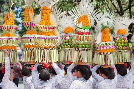 adult indonesia: DENPASAR, BALI ISLAND, INDONESIA - JUNE 11, 2016: Group of beautiful women in traditional Balinese costumes carry on head religious offering for hindu ceremony on parade at art and culture festival.