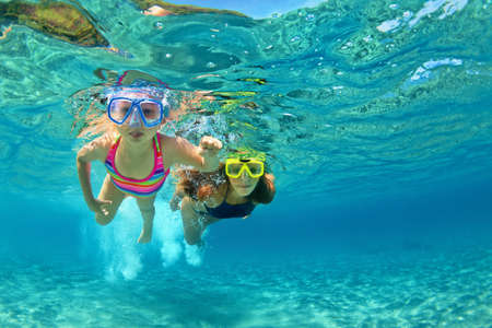 Happy family - mother with baby girl dive underwater with fun in sea pool. Healthy lifestyle, active parent, people water sport outdoor adventure, swimming lessons on beach summer holidays with child Foto de archivo
