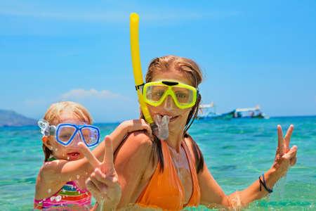 Familia feliz - madre con el bebé de buceo bajo el agua con la diversión en la piscina del mar. estilo de vida saludable, activa de los padres, la gente del deporte acuático aventura al aire libre, clases de natación en la playa Vacaciones de verano con el niño Foto de archivo - 69758990