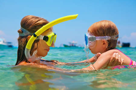 Happy family - mother with baby girl dive underwater with fun in sea pool. Healthy lifestyle, active parent, people water sport outdoor adventure, swimming lessons on beach summer holidays with child Banco de Imagens